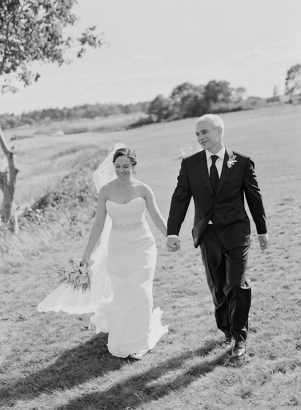 happy couple, bride and groom, outdoor wedding, lakeside wedding, lakefront wedding pictures, bride, groom, wedding dress, black and white wedding photo, smiling couple, couple holding hands