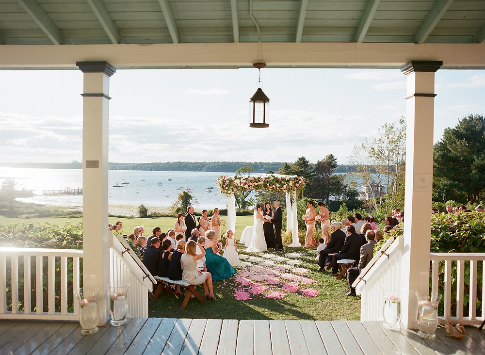 waterfront wedding, lakeside wedding, midwest wedding, small ceremony, outdoor wedding, pink flower wedding decor, lakeside wedding decor, summer wedding, southern wedding, porch, lantern, lake, wedding guests, arbor, wedding vows, pier, boats, glass pitchers, glass vases, wooden porch, painted porch