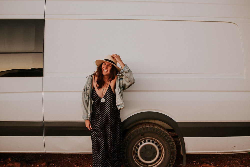 smiling young woman traveling cross country in a van