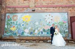 couple in front of mural by church