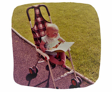 a baby reading a book in a buggy 1980s