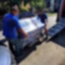 Luna's Piano Movers Loading an upright piano onto a moving truck via ramp