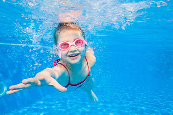 Portrait of little girl swimming underwater in pool.jpg