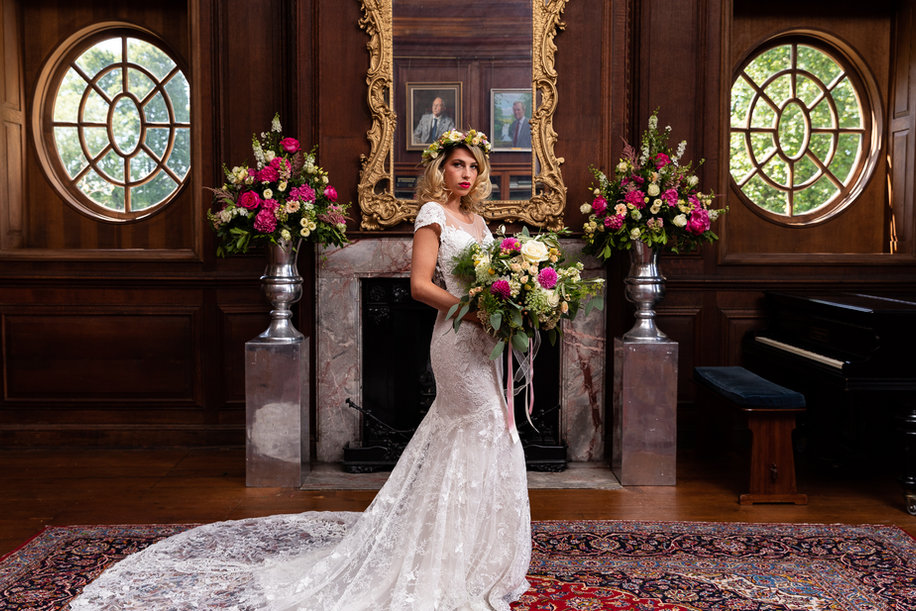 Woman-wearing-lace-fitted-wedding-dress-holding-a-huge-bouquet-in-front-a-huge-fireplace-at-Bradbourne-House-Kent