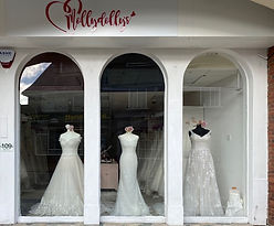 Front-of-Mollydollys-Boutique-shop-window-three-wedding-dresses-lace-fitted-ballgown