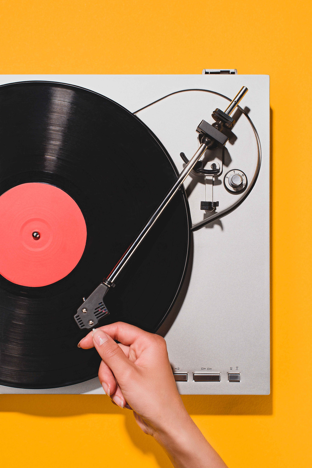 a picture of a hand  putting  the needle onto a vinyl record on a record player