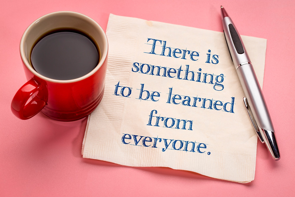 "A coffee cup, pen, and napkin with the words ""There is something to be learned from everyone"" written on the napkin."