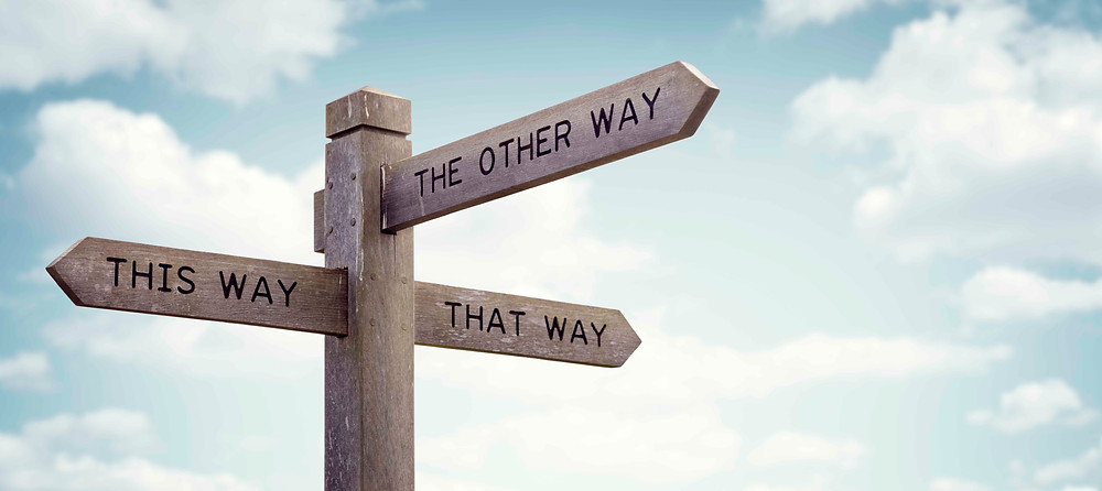 """A road  sign that points to """"this way,"""" """"that way,""""  and """"the other way."""""""