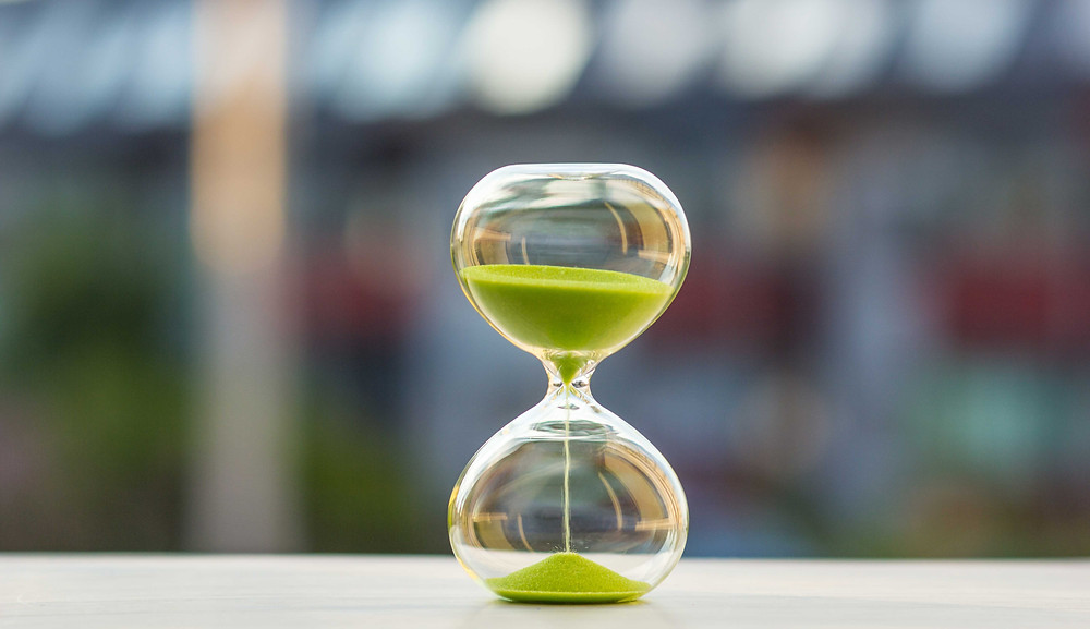 A picture of an hourglass with  green sand.