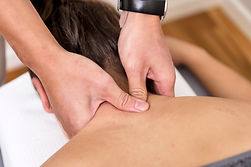 Physiotherapist using thumbs to release tension through patient neck