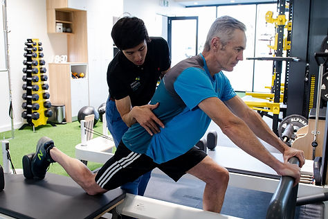 Physiotherapist Tim/Timothy Tey helping client by correcting exercise. The client is doing scooters on a reformer.