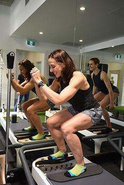 Woman squatting on a pilates reformer