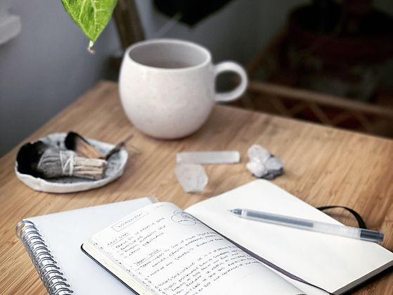 An open notebook on the table with a mug, crystal and pens surrounding it