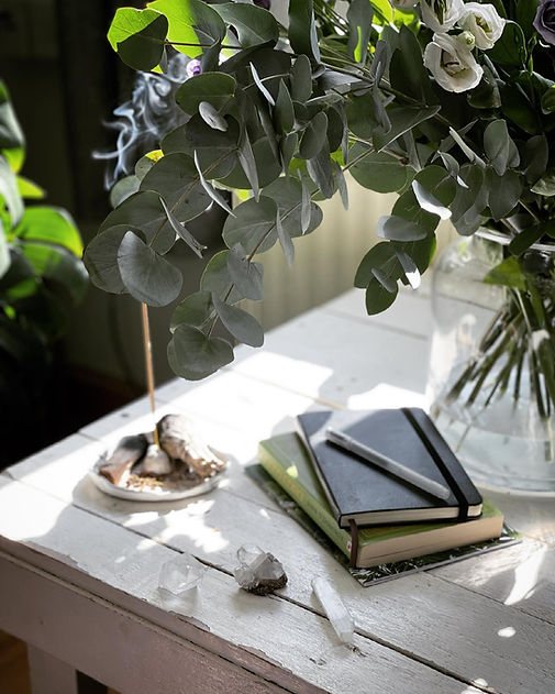 A stack of notebooks and books on white table, a lit incense is behind it. Greenery is also visible