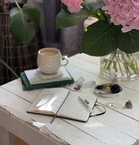An open notebook with a pen. In the background - a stuck of notebooks and cup of tea on top