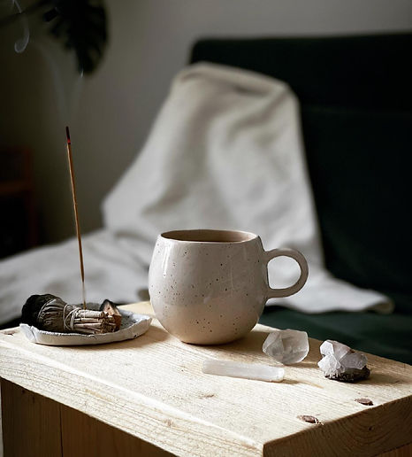 A photo of a big cup on the wooden table with incense and crystals near it