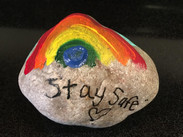 Rock decorated with a rainbow and a message to stay safe