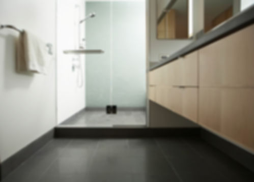 Modern bathroom design, wall hung vanity, wood vanity, black countertop, black tile floor, frameless swinging shower doors