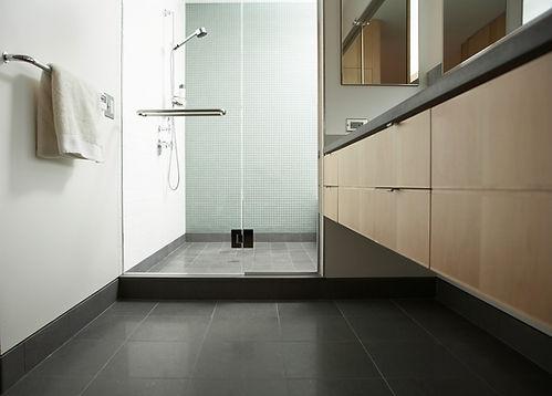 Modern bathroom design, wall hung vanity, wood vanity, black countertop, black tile floor, frameless swinging shower doors