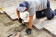 Worker setting paver bricks on large pat