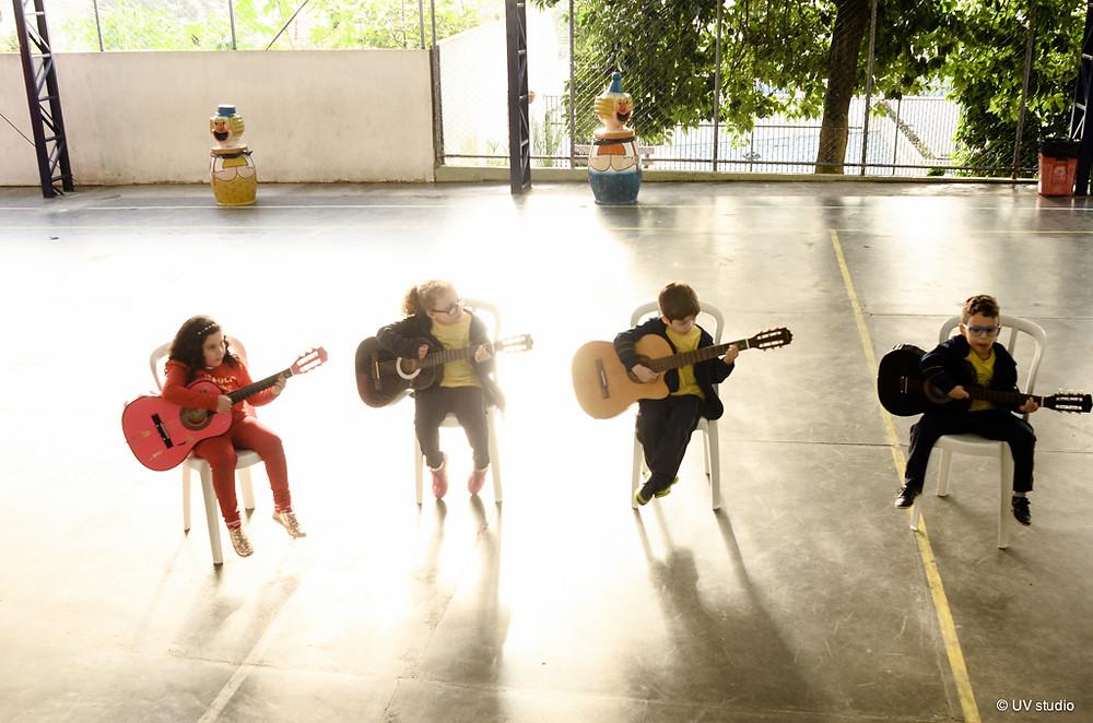Crianças tocando violão