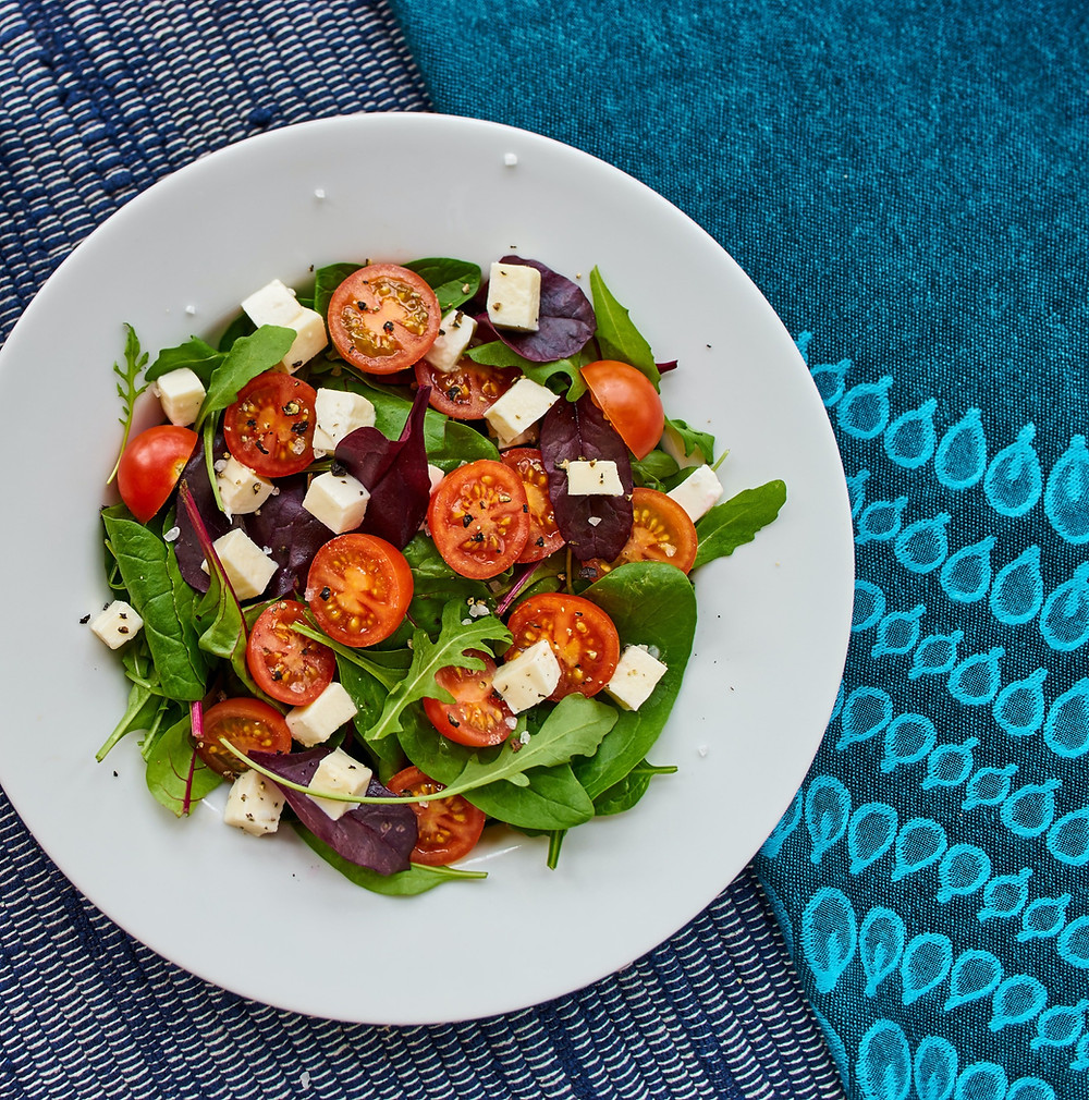 greek salad on a plate on top of a blue tablecloth / fully grown