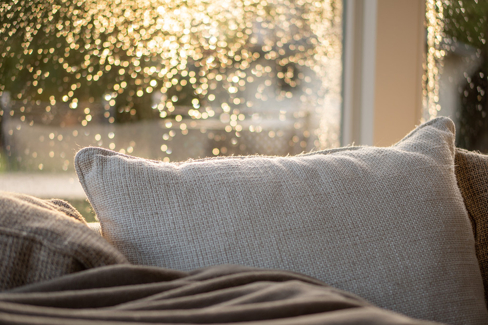 pillow on a sofa with a lit up rainy window behind
