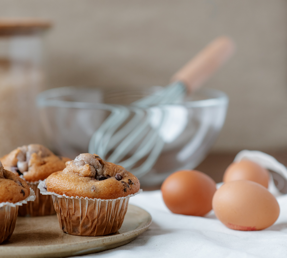 chocolate muffins next to eggs and a mixing bowl / fully grown