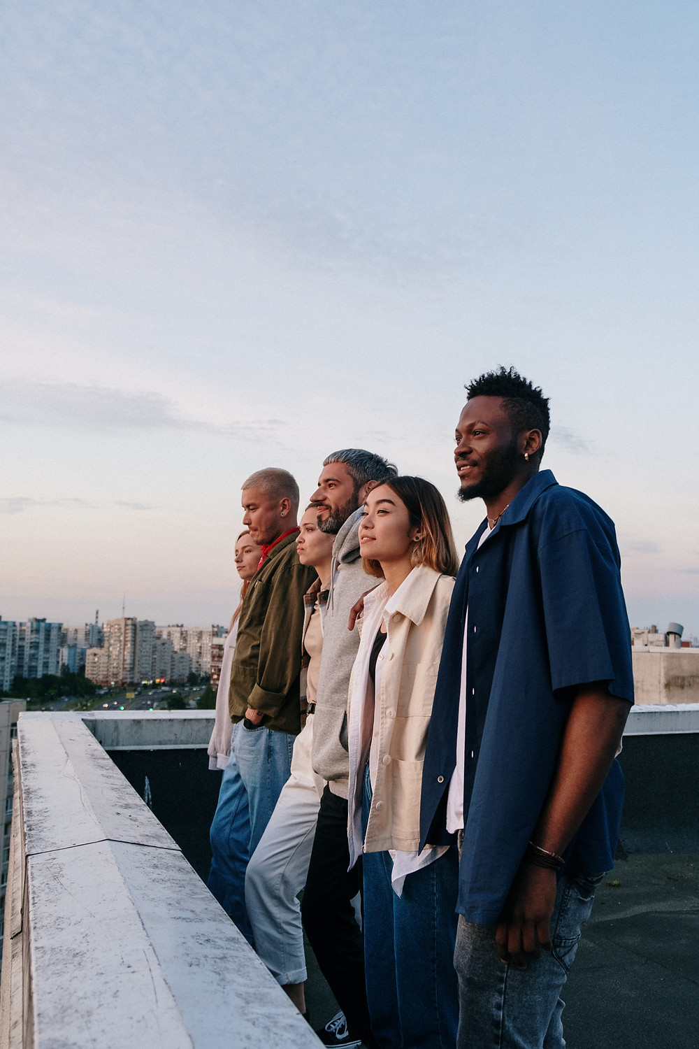 group of friends on top of a building looking at the view