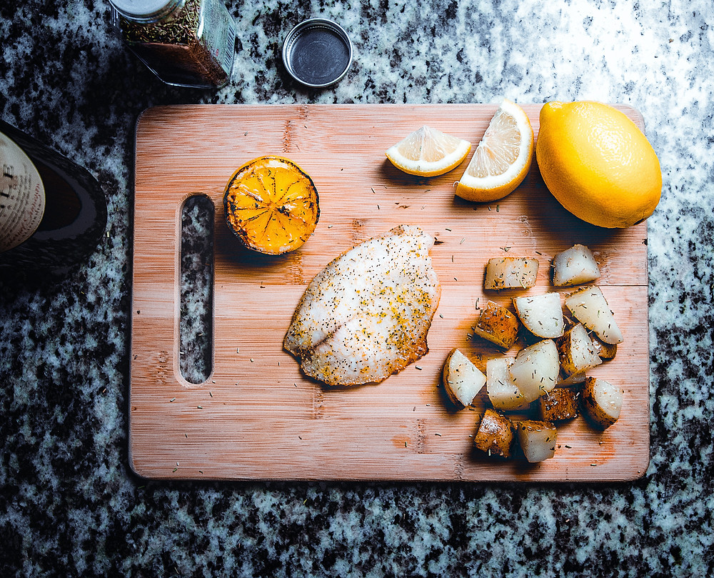Fish, potatoes and lemon on a chopping board   fully grown