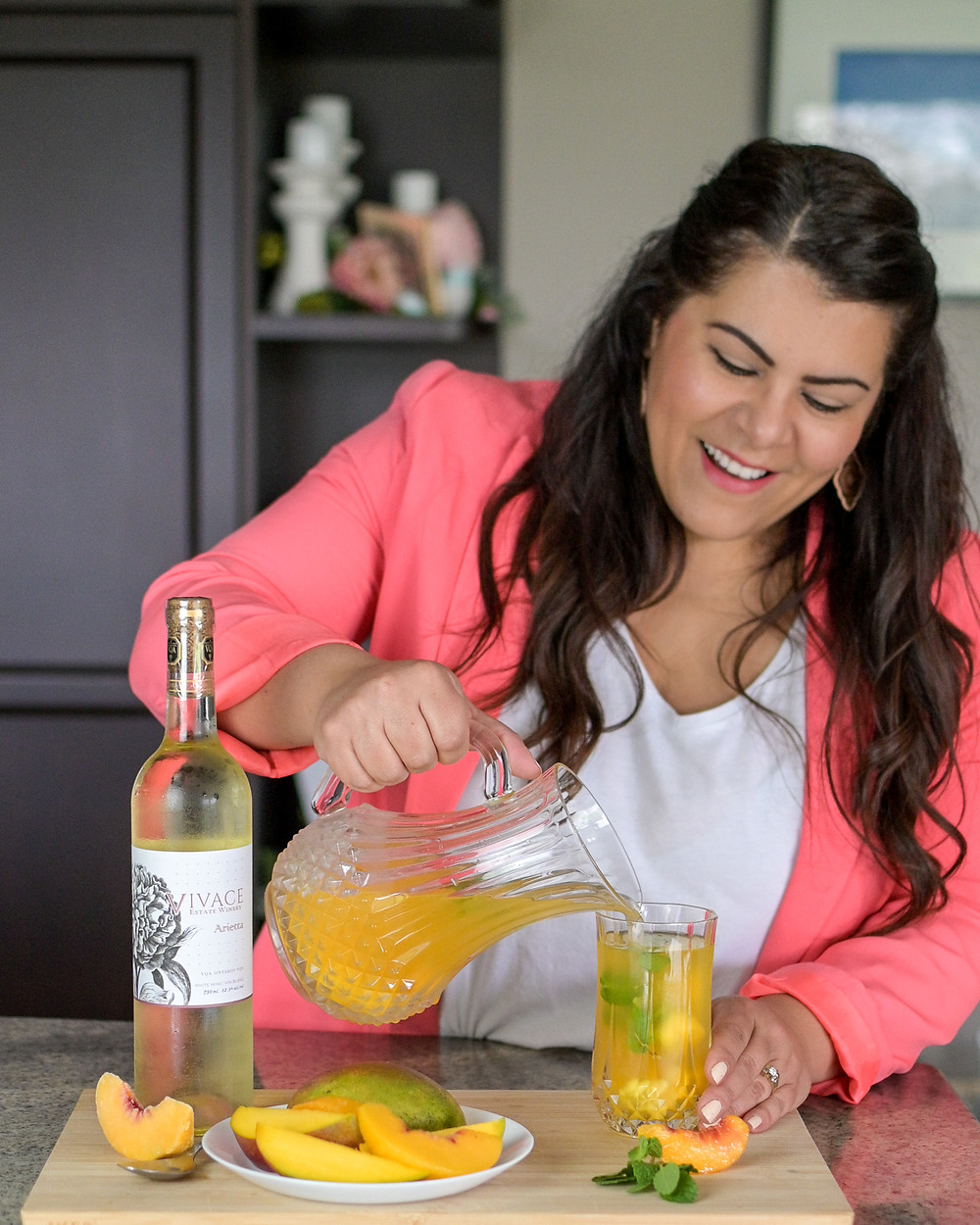 Mara from Joyful Hostest pouring the Vivace Peach Mango Sangria into a glass