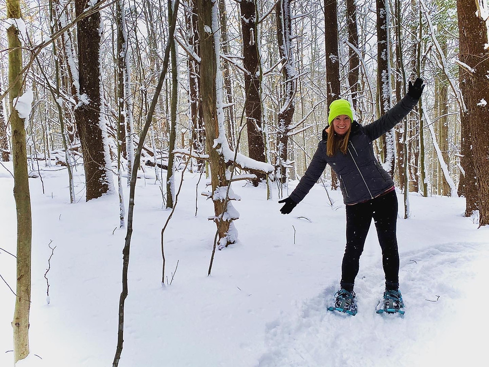 Woman walking through snowy forest wearing snowshoes.