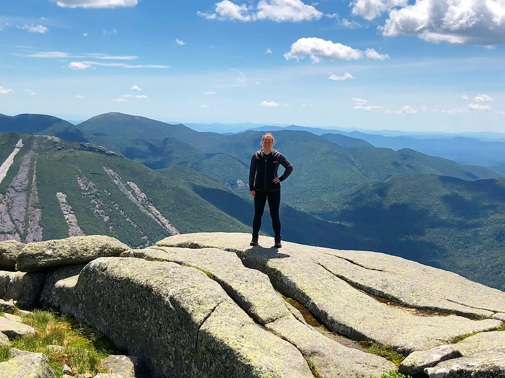 A woman standing at the top of the second highest mountain in New York.