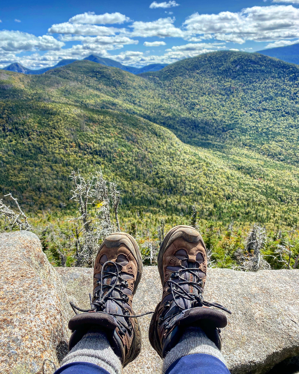 Hiking boots dangling over the ledge of a tall mountain.