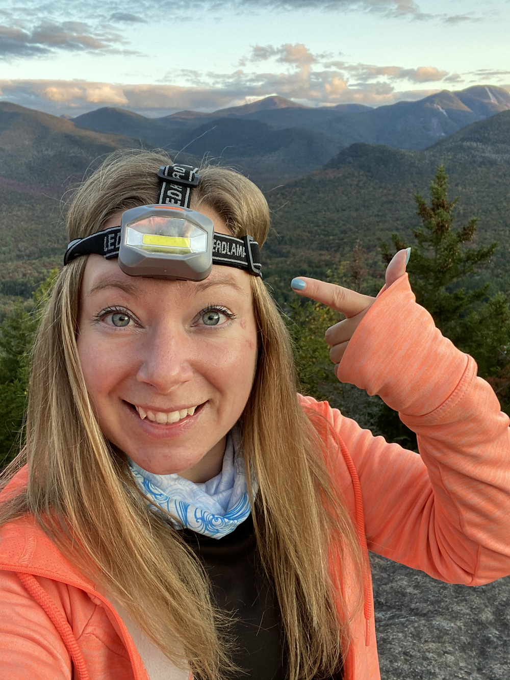 Woman standing on top of mountain pointing to the headlamp on her head.