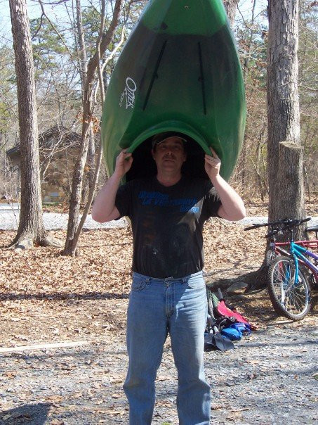 My dad, carrying a green kayak.