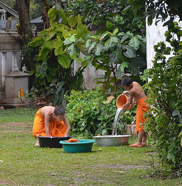 Two Thai boys washing their clothes at a temple in northern Thailand.