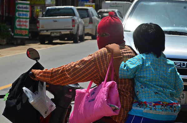 A mother takes her daughter to school in Thailand.