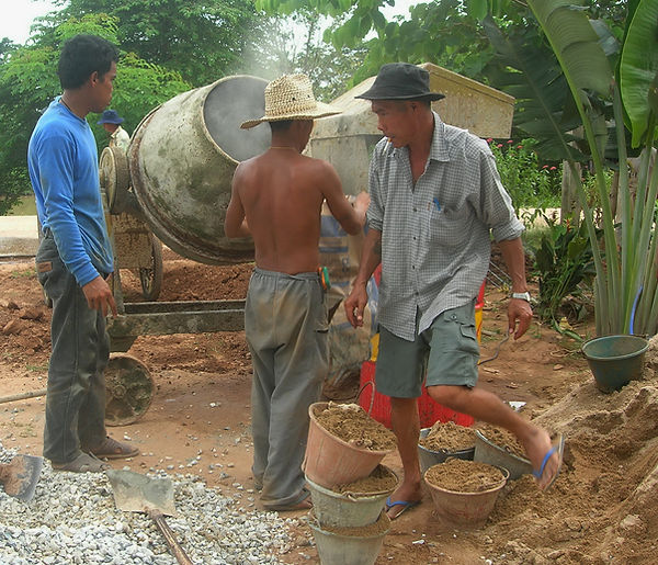 Workers mixing concrete in Thailand.