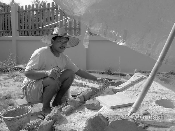 A Thai worker building a spirit house in rural Thailand.