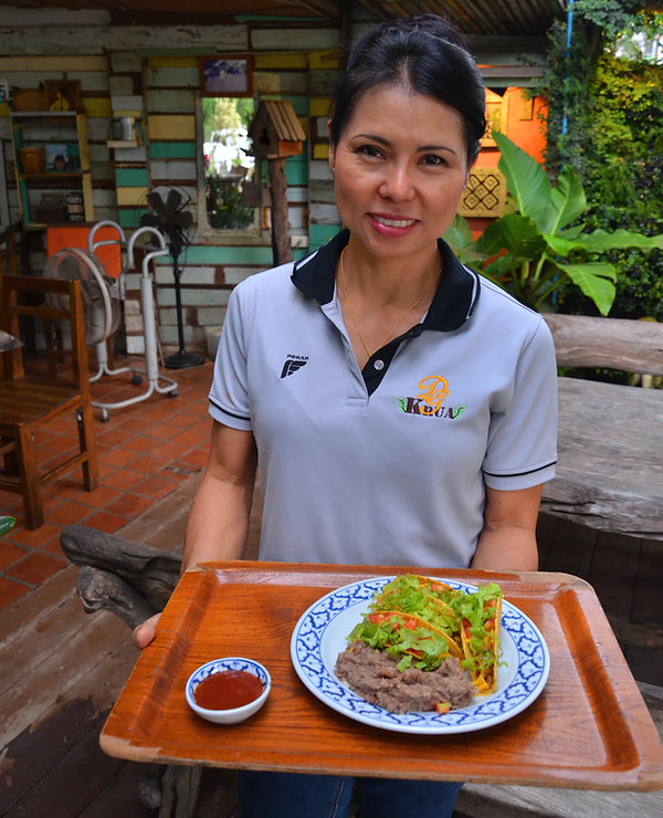 A lovely Thai lady serving tacos in Thailand.