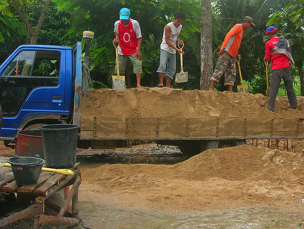 Unloading sand for a construction project in Thailand.