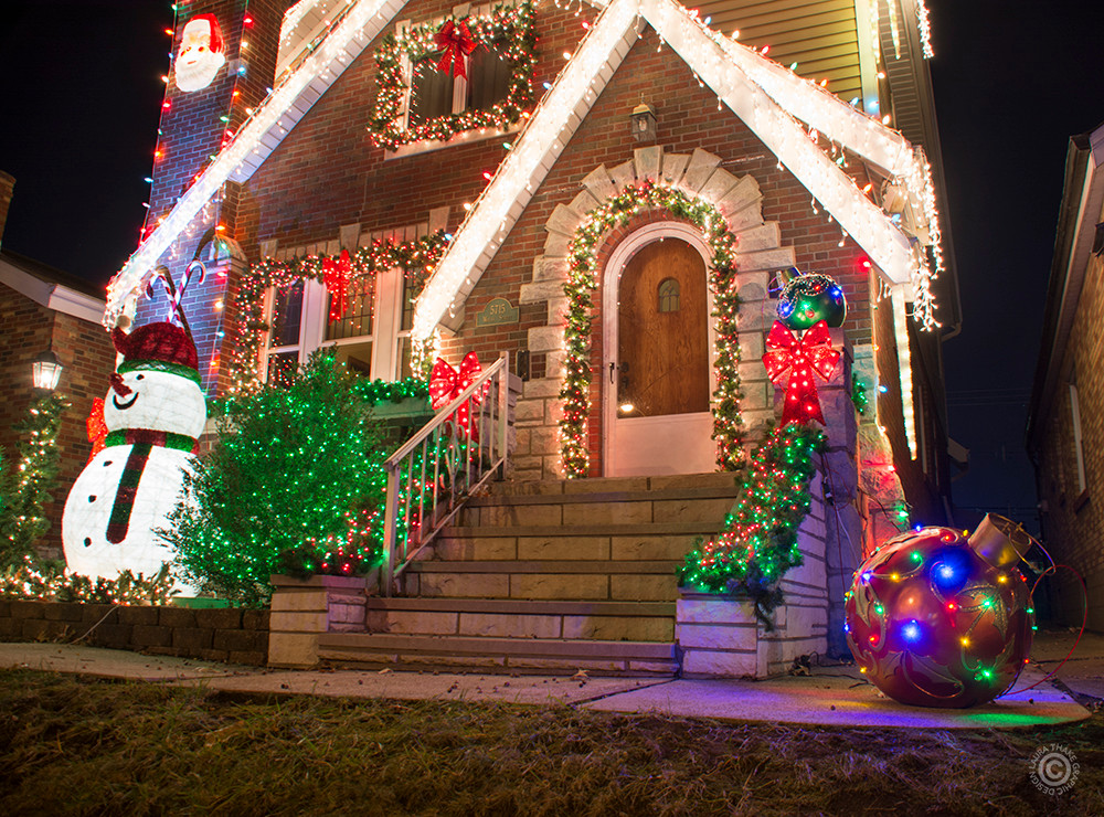 Christmas garland and lights on a house with giant Christmas ornaments.