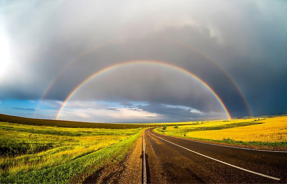 Rainbow over rural road landscape. Rainb