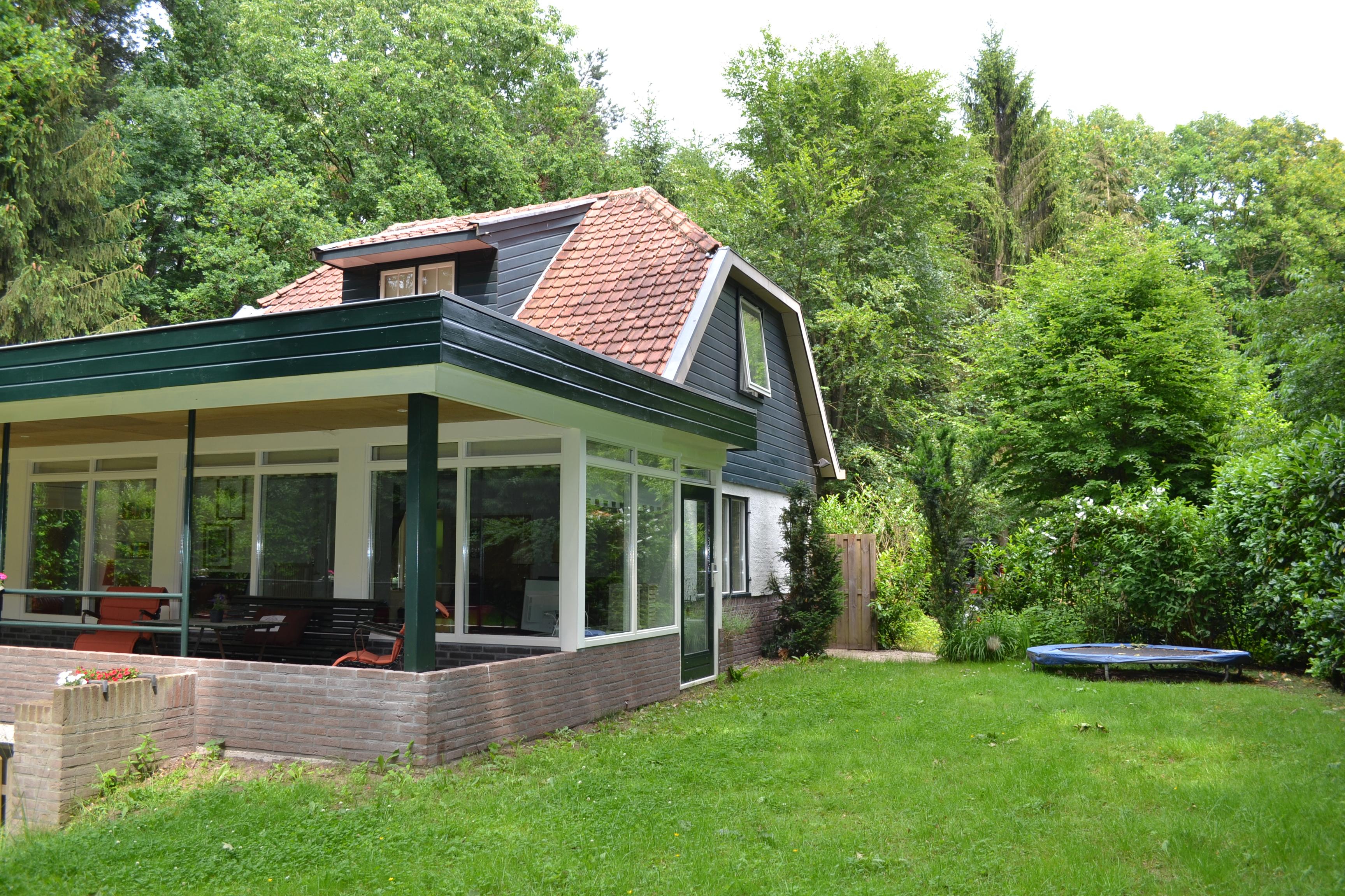 zijkant huis met trampoline