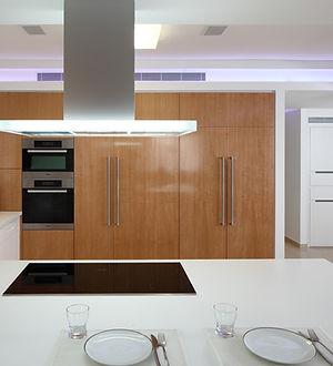 מטבח לבן מזווה דלתות מעץ מלא ואי מעליו קולט אדים