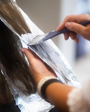 A stylist highlighting hair at Panache Hair Design in Shelton, CT.