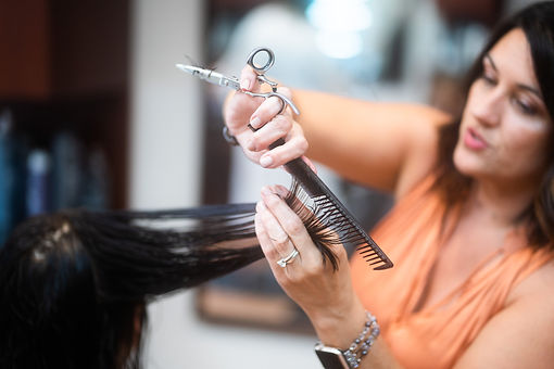 Amy, a stylist at Panache Hair Design in Shelton, CT, cutting a client's hair.