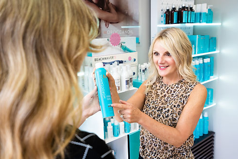 A stylist at Panache Hair Design in Shelton, CT helping a client pick out a Moroccanoil Product for their Loyalty Program.