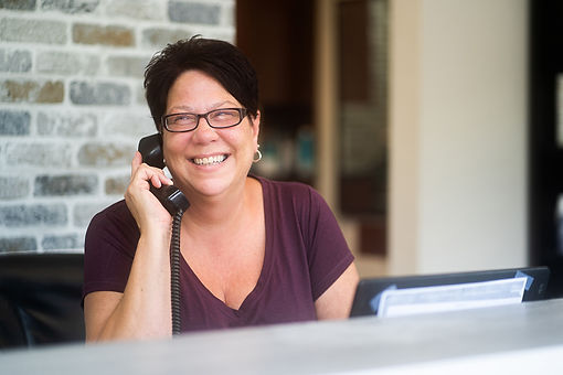 Lisa, the receptionist at Panache Hair Design in Shelton, CT, smiles as she talks with clients on the phone.